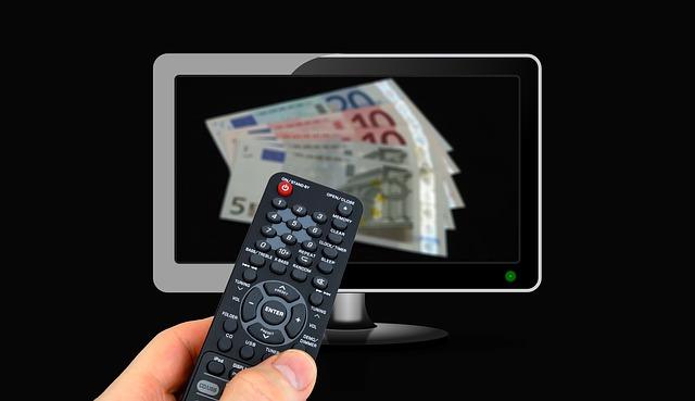 Ruka drží ovladač, v dáli televize.